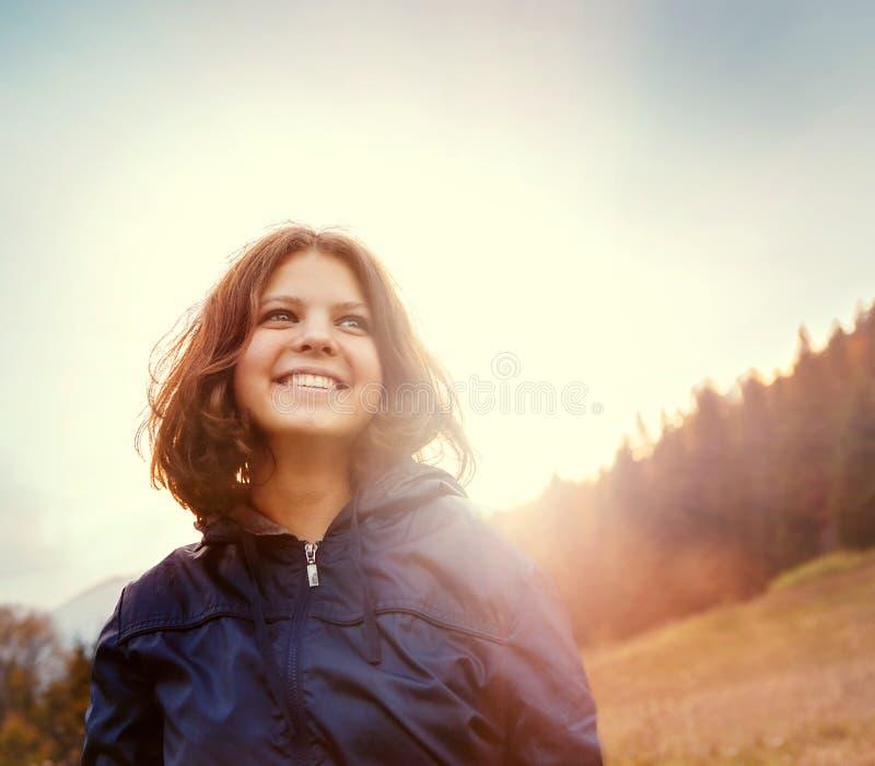 Jovem mulher de sorriso feliz na luz do por do sol no monte da montanha fotografia de stock