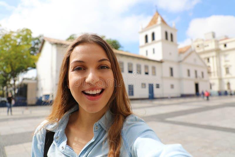A jovem mulher de sorriso feliz no autorretrato da tomada do centro da cidade de Sao Paulo com pátio faz o marco no fundo, Sao Pa imagens de stock