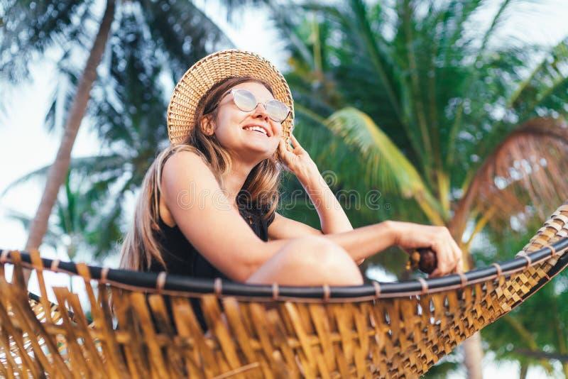 Jovem mulher de sorriso feliz no chapéu de palha nos óculos de sol que sentam-se no hammok e para apreciar a luz do sol da manhã fotografia de stock