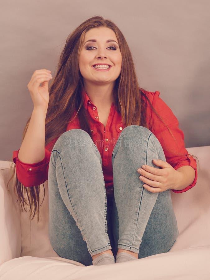 Jovem mulher de sorriso feliz no sofá imagens de stock