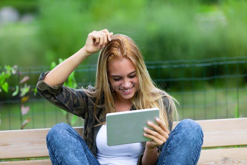 Jovem mulher de sorriso feliz que risca sua cabeça fotos de stock