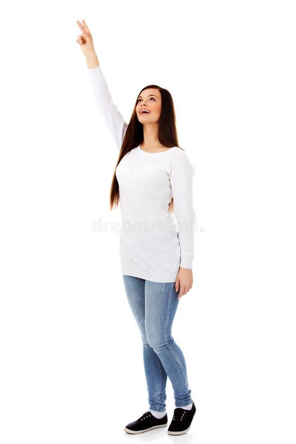 A jovem mulher de sorriso mostra algo imagens de stock royalty free