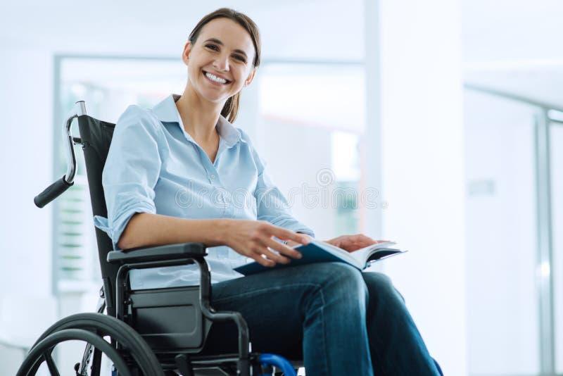 Jovem mulher de sorriso na cadeira de rodas fotografia de stock