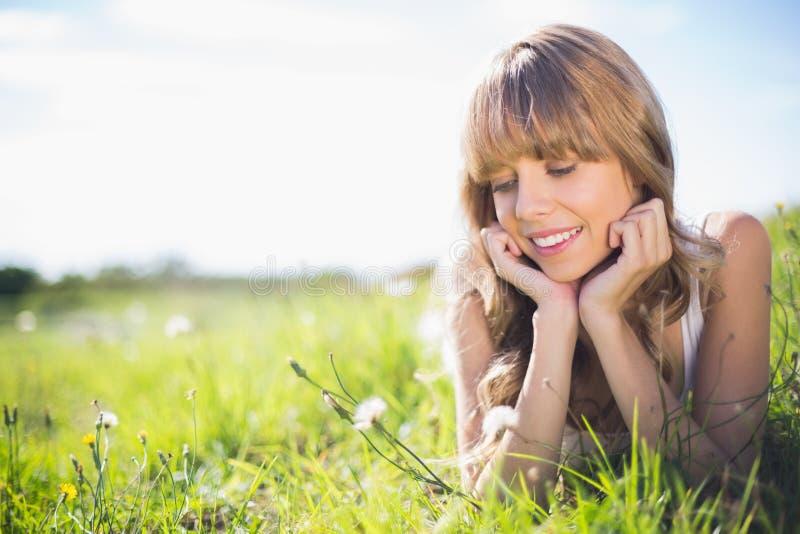 Jovem mulher de sorriso na grama que olha flores
