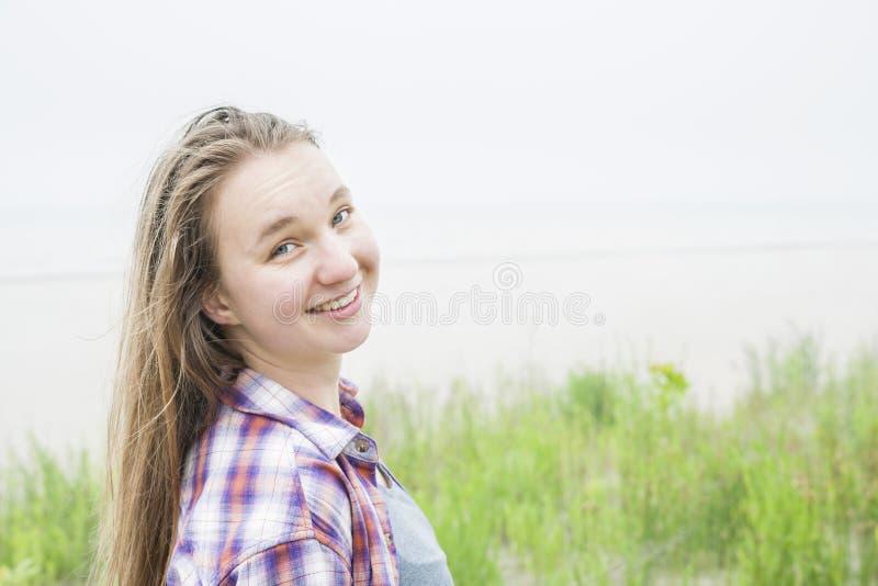 Jovem mulher de sorriso na praia imagem de stock