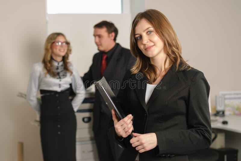 Jovem mulher de sorriso no escritório foto de stock royalty free