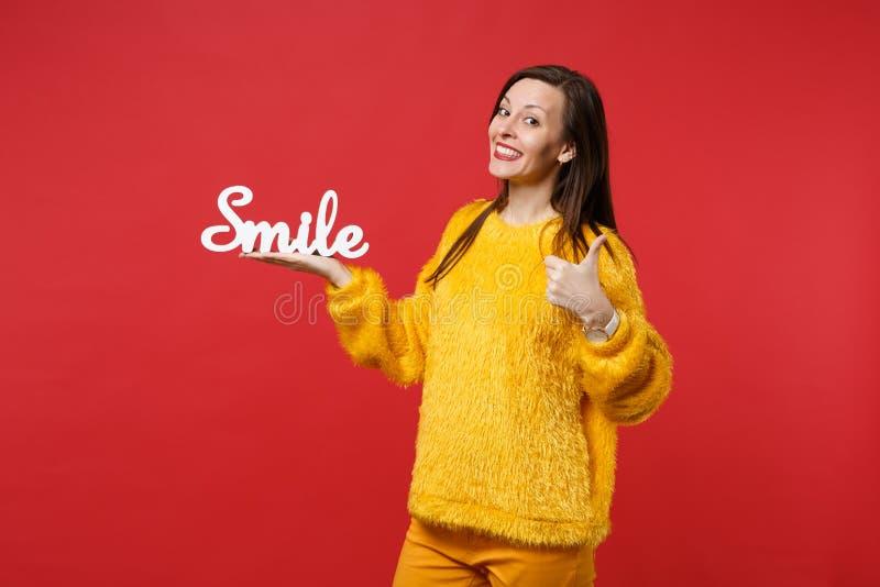 A jovem mulher de sorriso no polegar amarelo da exibição da camiseta da pele acima, guardando letras de madeira da palavra sorri  imagem de stock royalty free