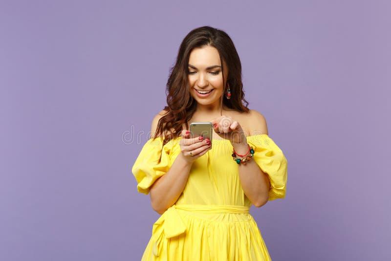 Jovem mulher de sorriso no vestido amarelo do verão usando o telefone celular, mensagem de datilografia dos sms isolada na parede imagens de stock