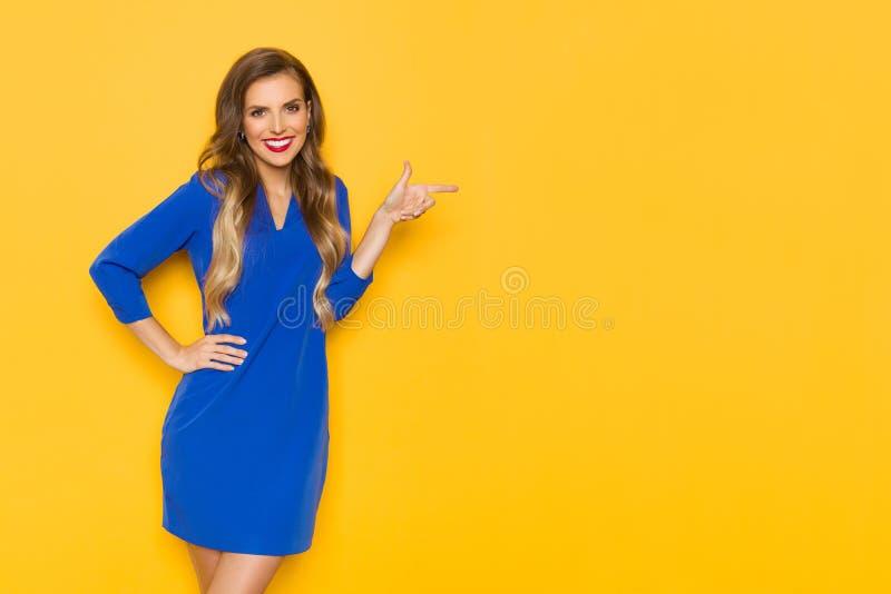 A jovem mulher de sorriso no vestido azul é apontando e de vista a câmera fotografia de stock royalty free