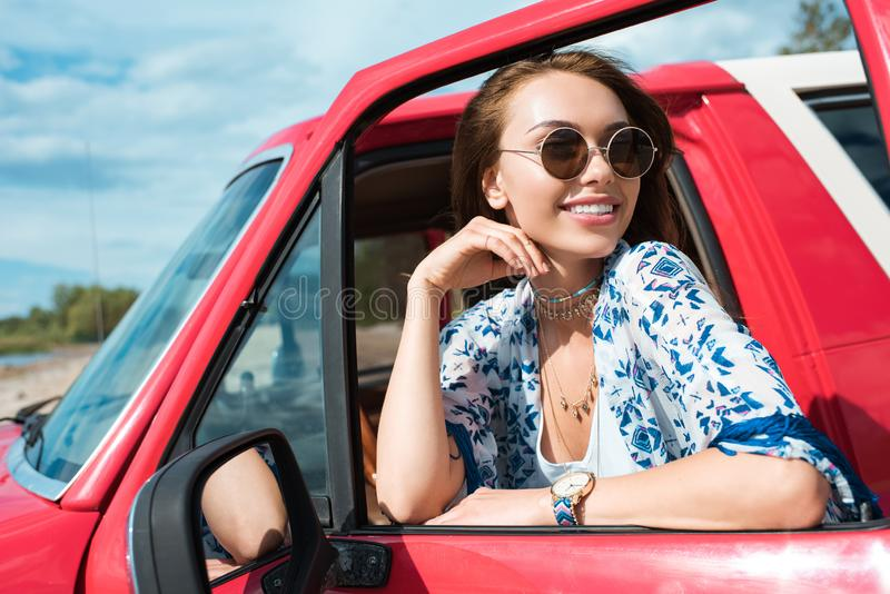 jovem mulher de sorriso nos óculos de sol no carro foto de stock royalty free