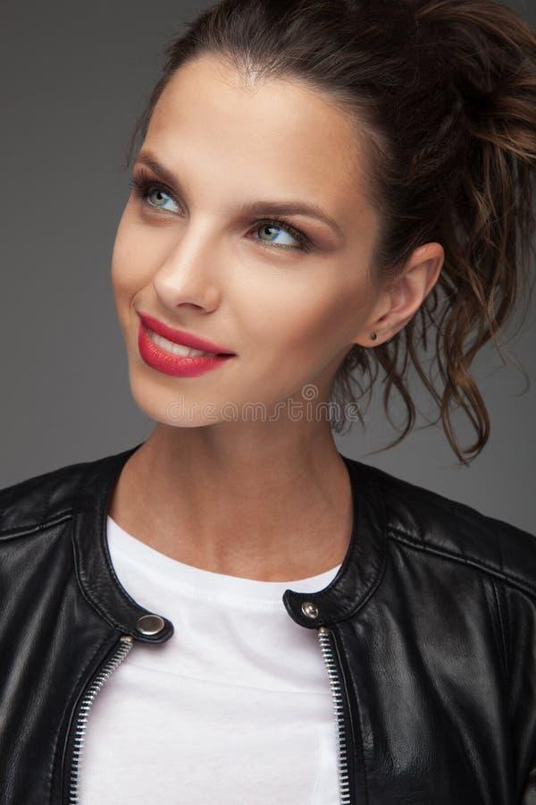 A jovem mulher de sorriso olha acima a um lado imagem de stock