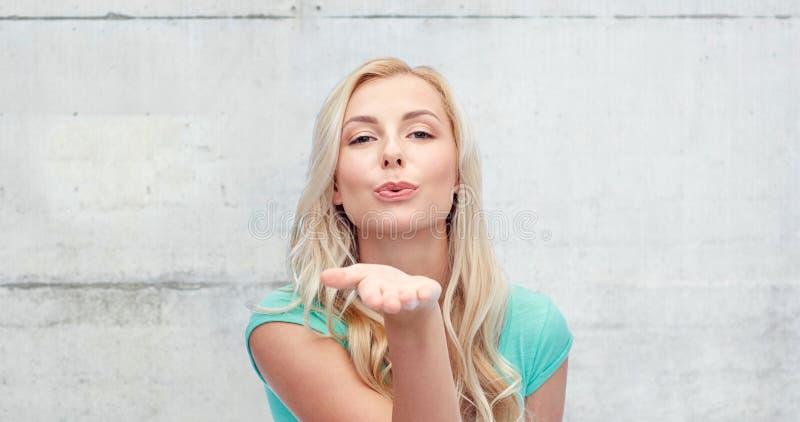 Jovem mulher de sorriso ou menina adolescente que enviam o beijo do sopro imagem de stock royalty free