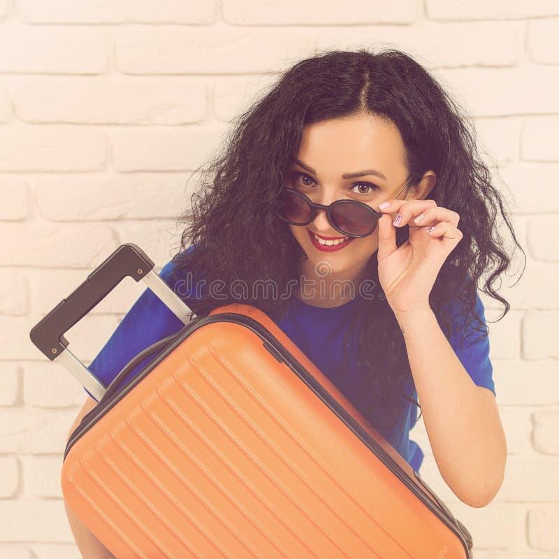 Jovem mulher de sorriso que abraça sua mala de viagem alaranjada A menina ocasional está pronta para viajar Mulher feliz nos ócul imagem de stock royalty free