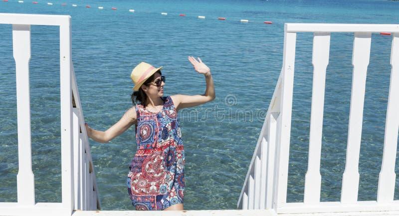 Jovem mulher de sorriso que acena em um fundo do mar imagem de stock