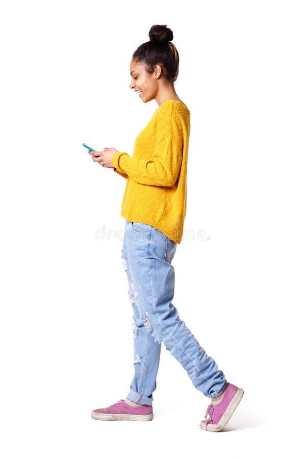 Jovem mulher de sorriso que anda e que olha o telefone celular imagens de stock
