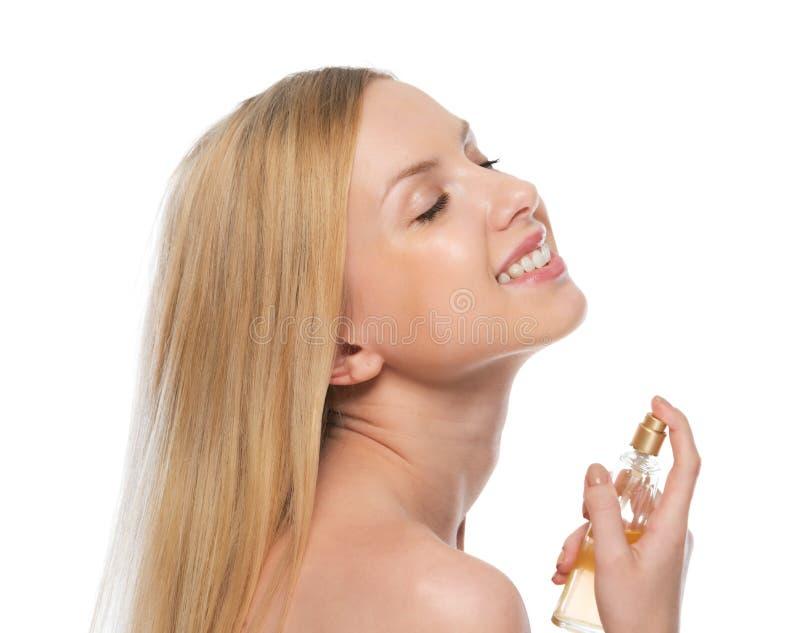 Jovem mulher de sorriso que aplica o perfume fotos de stock