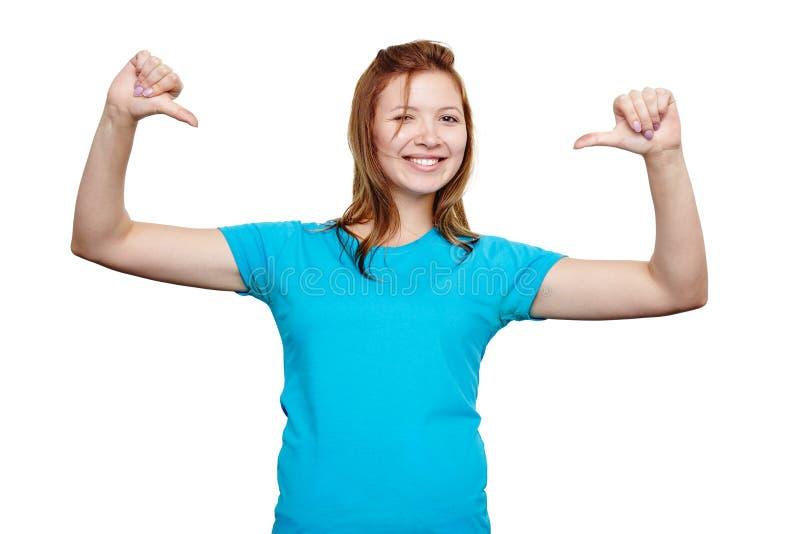 Jovem mulher de sorriso que aponta nsi mesma Projeto do t-shirt fotografia de stock royalty free