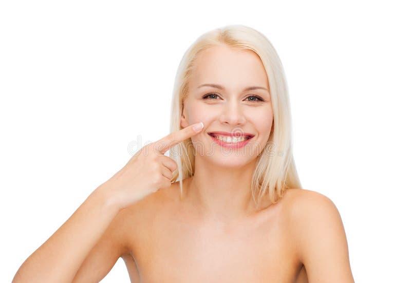 Jovem mulher de sorriso que aponta a seu nariz imagem de stock royalty free