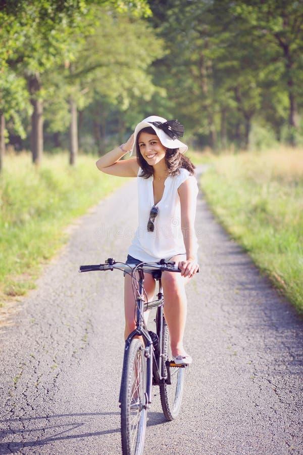 Jovem mulher de sorriso que biking em uma estrada secundária imagem de stock