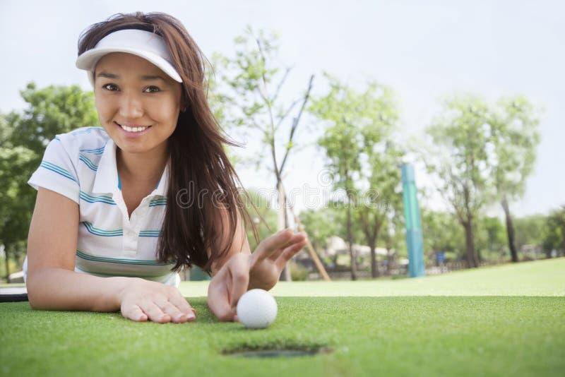 Jovem mulher de sorriso que encontra-se para baixo em um campo de golfe que prepara-se para passar rapidamente a bola no furo fotografia de stock