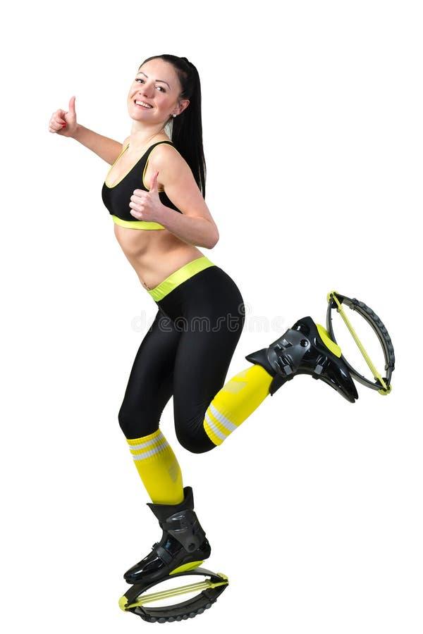 A jovem mulher de sorriso que faz exercícios no kangoo salta sapatas imagem de stock