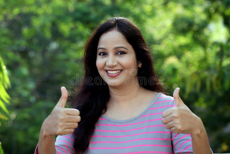 A jovem mulher de sorriso que faz os polegares levanta o gesto imagem de stock royalty free