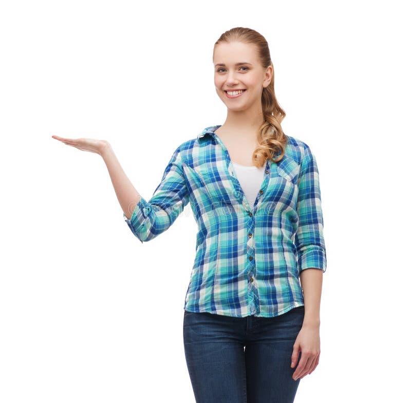 Jovem mulher de sorriso que guarda algo disponível imagem de stock