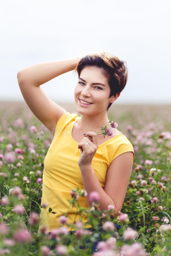 Jovem mulher de sorriso que guarda a flor selvagem e que levanta no campo fotos de stock royalty free