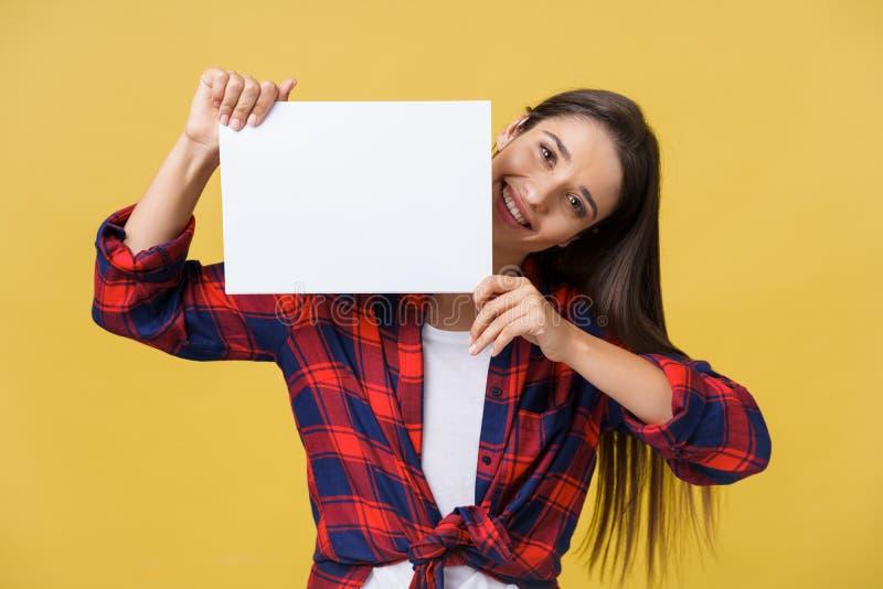 Jovem mulher de sorriso que guarda a folha do Livro Branco Retrato do estúdio no fundo amarelo imagem de stock