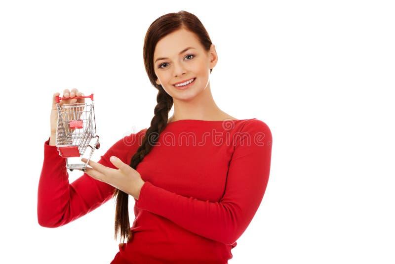 Jovem mulher de sorriso que guarda o carrinho de compras vazio pequeno fotografia de stock