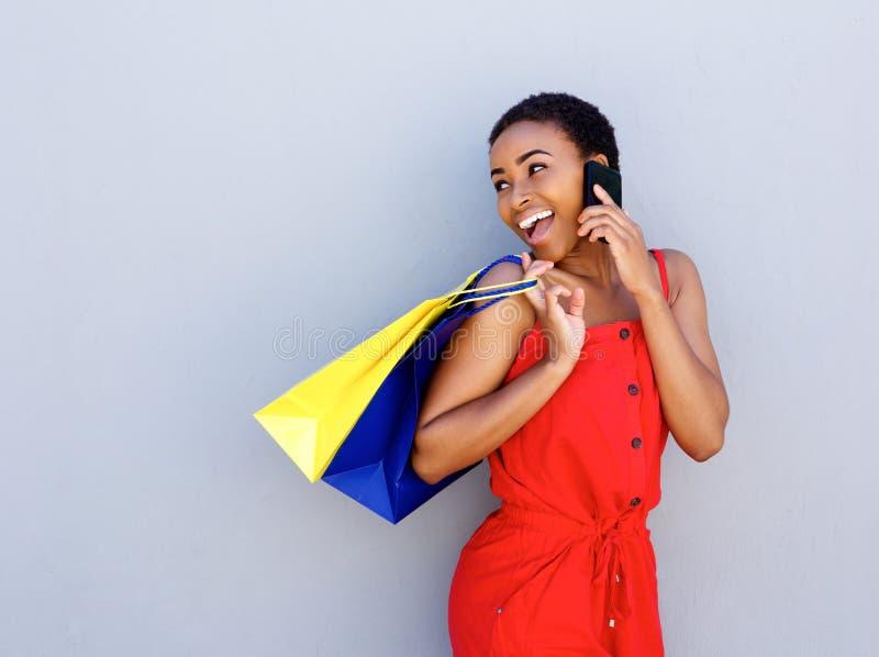 Jovem mulher de sorriso que guarda os sacos de compras que falam no telefone celular imagens de stock royalty free
