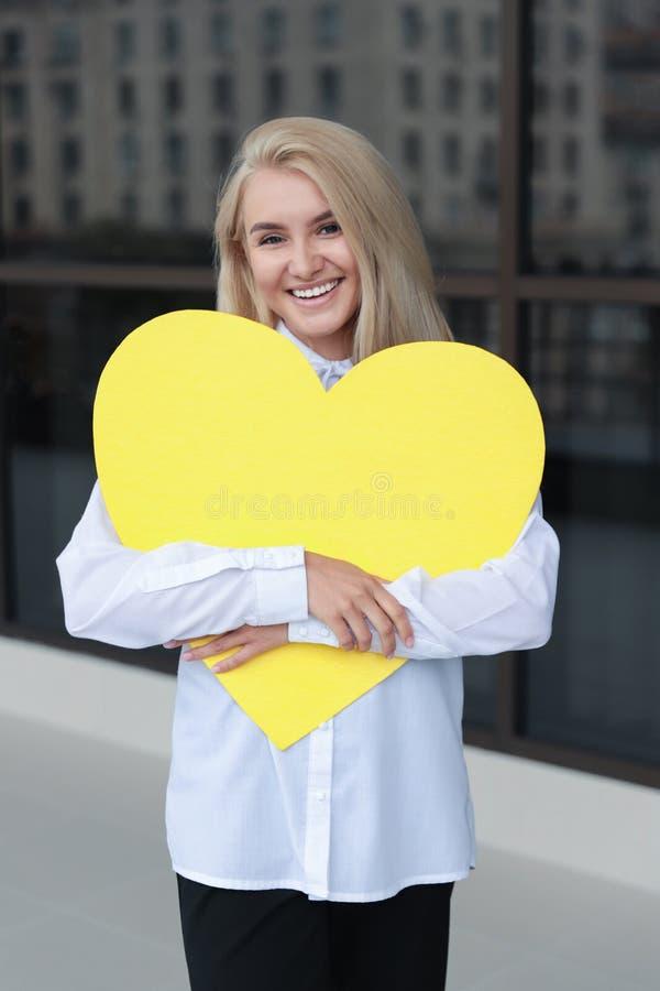 Jovem mulher de sorriso que guarda uma placa amarela nas m?os imagens de stock royalty free