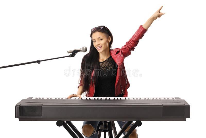 Jovem mulher de sorriso que joga um teclado e que canta em um microfone fotografia de stock