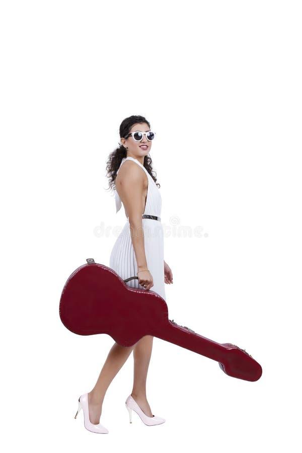 Jovem mulher de sorriso que levanta com guitarra imagens de stock