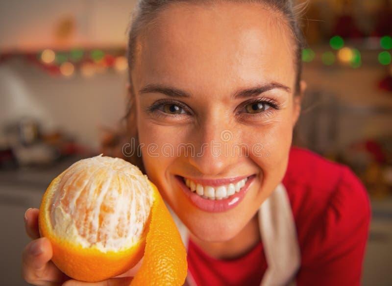 Jovem mulher de sorriso que mostra a laranja na cozinha fotos de stock royalty free