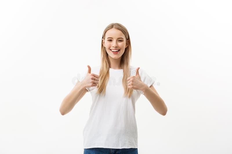 Jovem mulher de sorriso que mostra os polegares acima e a vista da câmera sobre o fundo branco imagem de stock