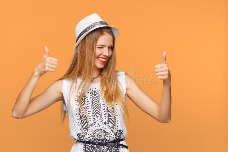 Jovem mulher de sorriso que mostra os polegares acima, isolado no fundo cinzento Menina feliz que pisc alegremente foto de stock
