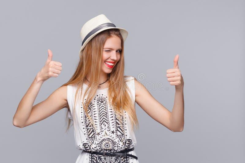 Jovem mulher de sorriso que mostra os polegares acima, no fundo cinzento Menina feliz que pisc alegremente imagem de stock