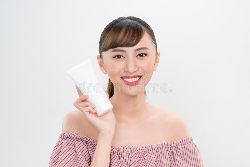 Jovem mulher de sorriso que mostra produtos do skincare fotografia de stock royalty free