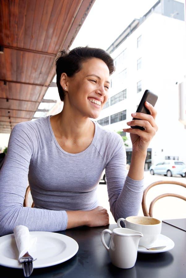 Jovem mulher de sorriso que olha o telefone celular no café fotografia de stock royalty free
