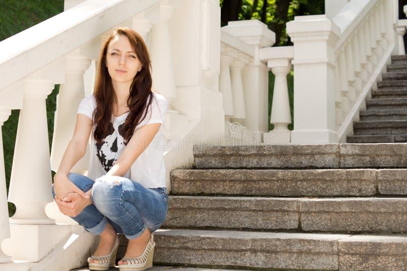 Jovem mulher de sorriso que relaxa em uma escadaria foto de stock