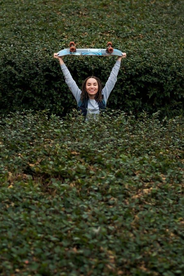 Jovem mulher de sorriso que salta entre arbustos verdes fotografia de stock