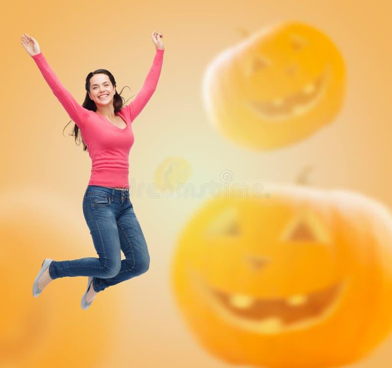 Jovem mulher de sorriso que salta no ar fotografia de stock