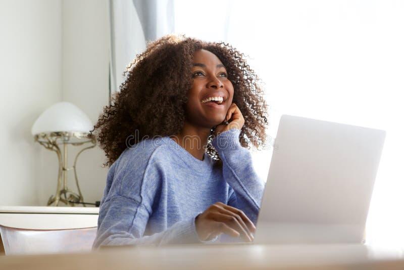 Jovem mulher de sorriso que senta-se em casa com portátil e que olha afastado fotos de stock