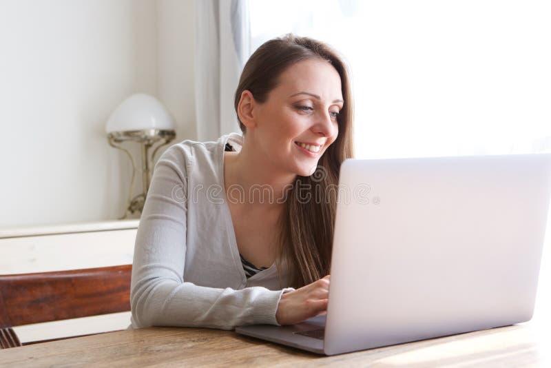 Jovem mulher de sorriso que senta-se em casa olhando o portátil imagens de stock royalty free