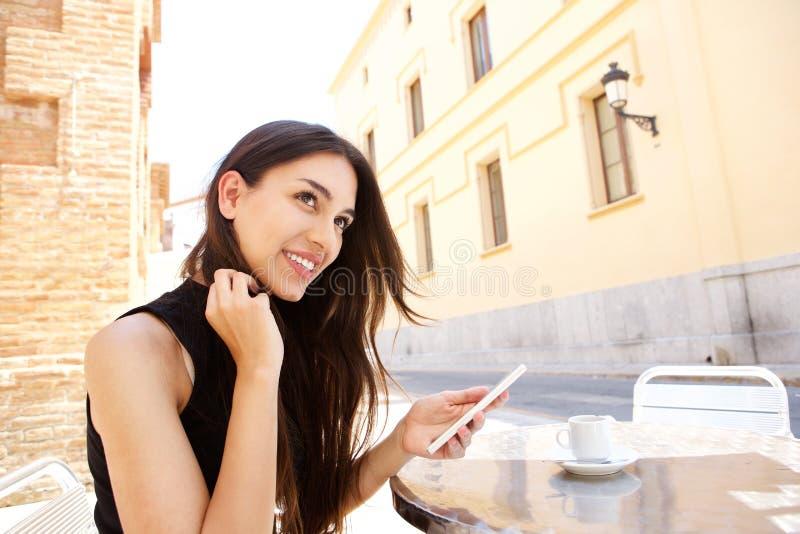 Jovem mulher de sorriso que senta-se fora no café com telefone celular fotografia de stock