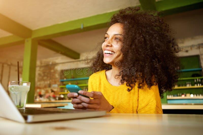 Jovem mulher de sorriso que senta-se no café com telefone celular fotos de stock