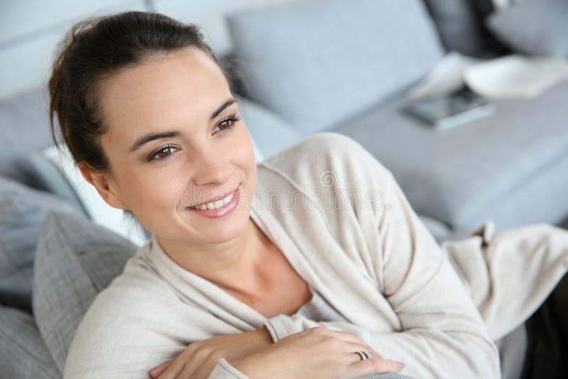 Jovem mulher de sorriso que senta-se no sofá imagem de stock royalty free