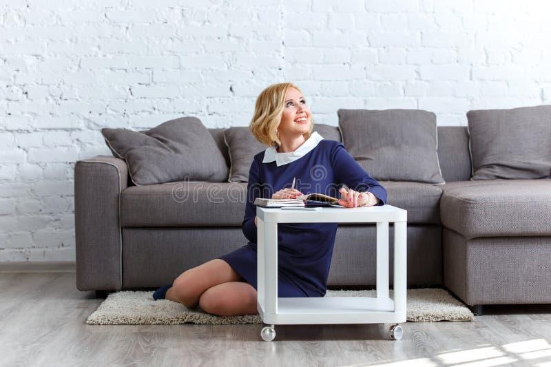 Jovem mulher de sorriso que senta-se no tapete com seu caderno imagem de stock royalty free