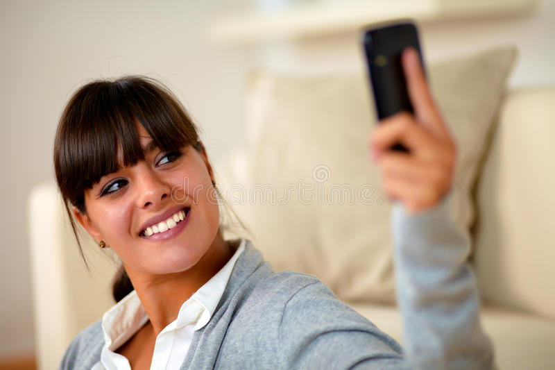 Jovem mulher de sorriso que toma uma foto com telemóvel foto de stock royalty free